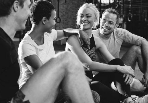 Diverse group of fit people in sportswear talking and laughing together while sitting on the floor after a gym workout class
